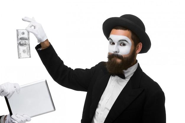 Рука бизнесмена в виде мима извлекает деньги из планшетного пк
