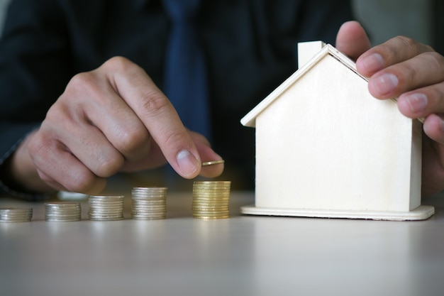 The businessman's hand is holding a coin putting it in a stack and capturing the house model.