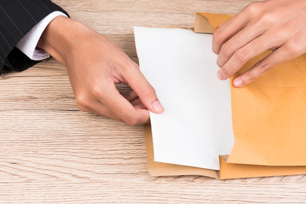 A businessman's hand opens a brown envelope on a desk.