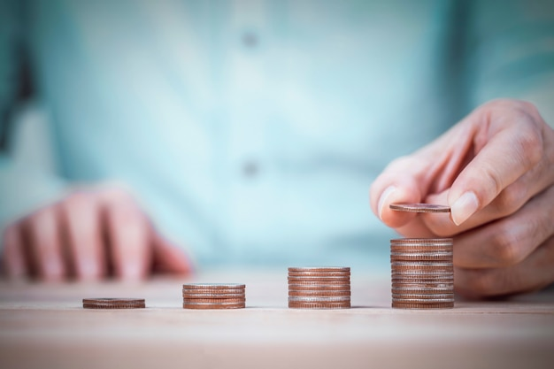 Businessman's hand putting coin on coin stacks on wooden table and mint shirt background