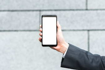 Businessman's hand showing blank mobile screen against blurred backdrop