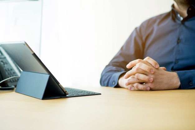 Businessman's hand with laptop over wooden desk