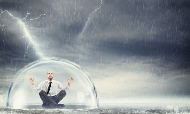 폭풍 동안 구체 안에 안전하게 사업가입니다. 재정적, 경제적 평온을 보호하십시오