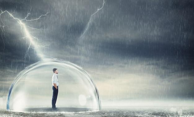 폭풍 동안 구체 안에 안전하게 사업가입니다. 위기 개념으로부터 보호