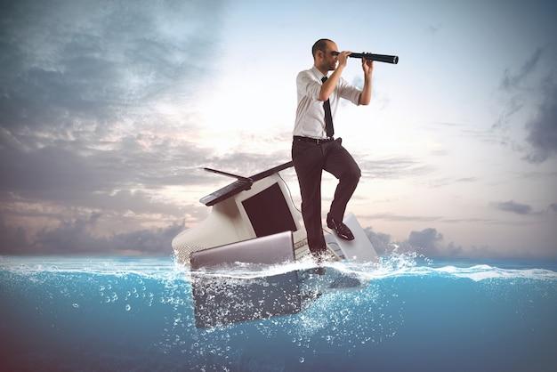 海でラップトップとパソコンで航海するビジネスマン