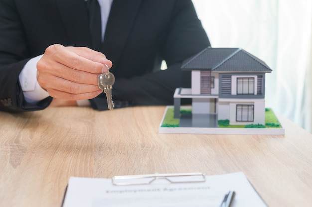 Businessman or sale man giving a house key after sign loan agreement