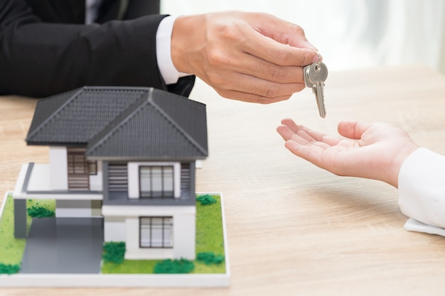 Businessman or sale man giving a house key to woman - buying home concept
