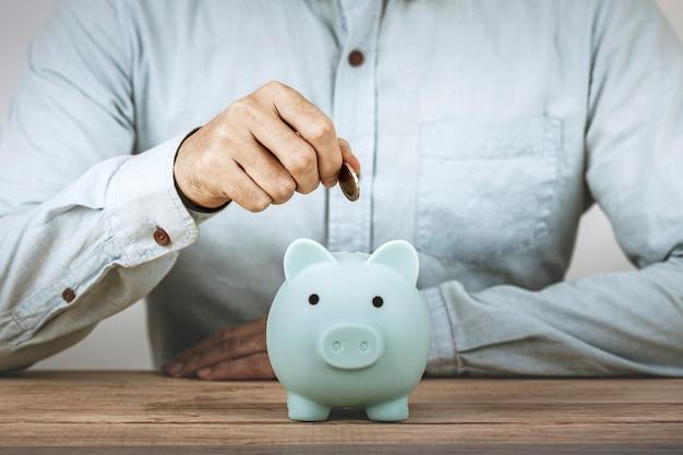 ビジネスマンは貯金箱にお金を節約し、手は貯金箱にお金のコインを入れて節約します