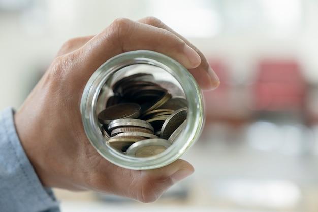 Бизнесмен, экономя деньги концепции. рука, держащая монеты, кладет в кувшин из стекла