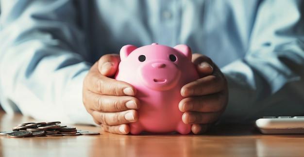 Бизнесмен, экономя деньги концепции. рука держит в защиту копилку