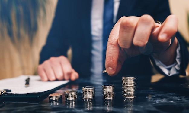Бизнесмен, экономя деньги, кладет монеты на стеки. концепция финансов и бухгалтерского учета.