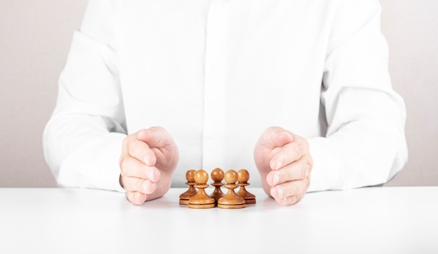 Businessman saving small group of chess under his hands. concept of leadership, teamwork and insurance.