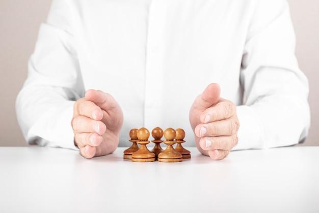 Бизнесмен, спасая небольшую группу шахмат под его руками. концепция лидерства, совместной работы и страховки.