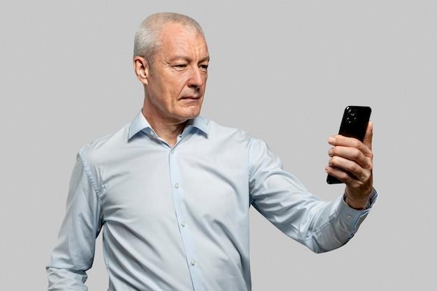 電話のセキュリティ技術のロックを解除するために彼の顔をスキャンするビジネスマン