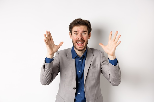 Бизнесмен кричит и пожимает руки в панике, выглядит встревоженным и встревоженным, кричит в камеру, стоя в костюме на белом фоне.