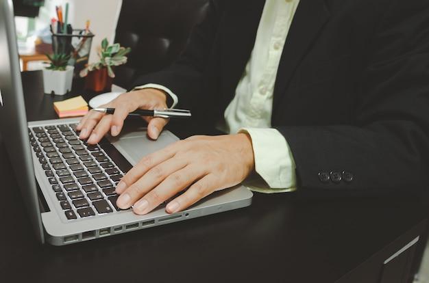 Seacrh бизнесмена находит информацию в социальных сетях интернета с портативным компьютером на столе. работа на дом.