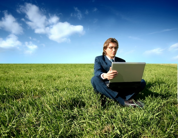 Businessman seated on grass field working with laptop