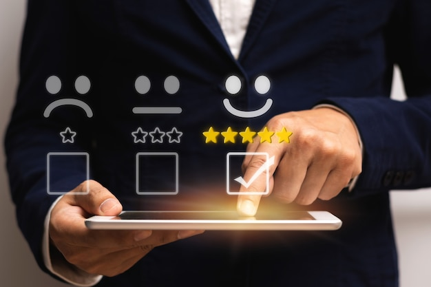 Бизнесмен выбирает смайлик с улыбкой на лице 5 звезд в контрольном списке и держит планшет, чтобы просмотреть хороший рейтинг