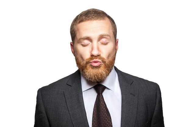 사업가는 눈을 감고 키스를 보냅니다. 흰색에..