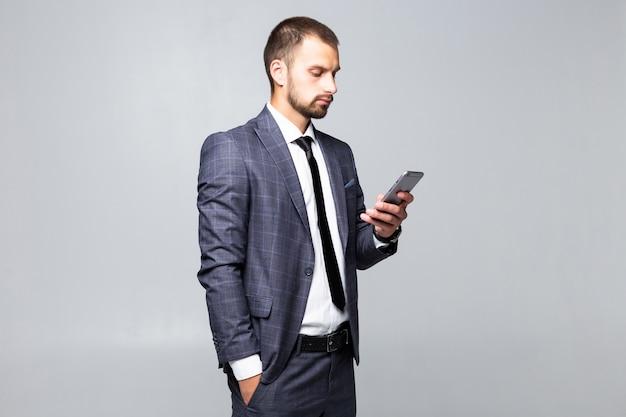 白い背景で隔離された彼の携帯電話でメッセージを送信するビジネスマン