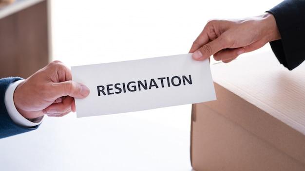 Бизнесмен посылая письмо отставки к исполнительному боссу работодателя на столе для того чтобы уйти в отставку увольняет контракт, размещение работы и концепция вакансий.