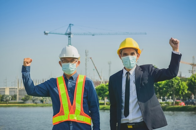 안면 마스크를 착용하는 사업가 수석 엔지니어 사이트 건설에 성공을 손을 보여