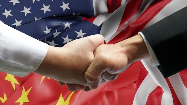 ビジネスマンは、中国とアメリカの手を振る旗を握手します。
