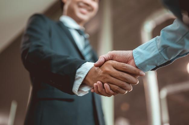 사업가는 비즈니스에 대해 이야기하기 전에 악수하고 서로를 알아갑니다.