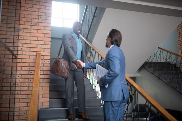 악수 하는 사업가. 계단에서 만나는 동안 동료와 악수하는 검은 피부의 사업가