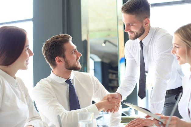 Businessman shaking hands to seal a deal with his partner and colleagues in office.