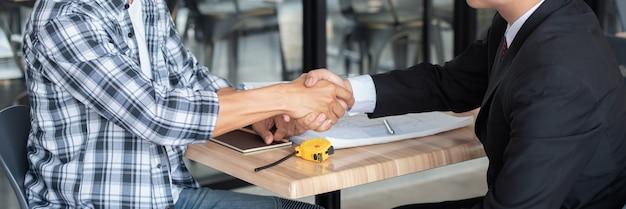 Бизнесмен тряся руки с построителем на строительной площадке, концом вверх.