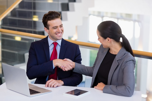 Businessman shaking hands with colleague at desk