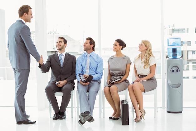 インタビューのために待っている人のほかに男性と手を振るビジネスマン