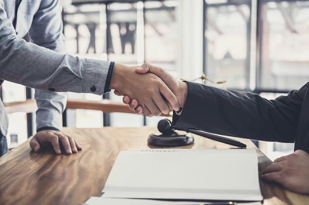 Бизнесмен, обменивающийся рукопожатием с профессиональным юристом-мужчиной после обсуждения хорошей сделки