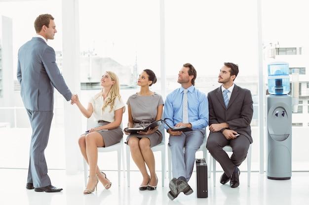 インタビューを待っている人のほかに女性と握手をする実業家