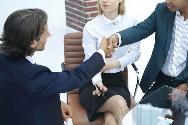 交渉が成功した後、パートナーの手を振るビジネスマン。