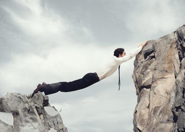 Бизнесмен форма своим телом мост между двумя горами