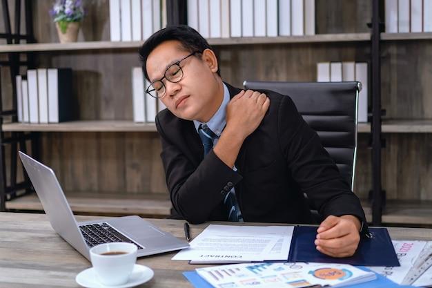 オフィスで働くことからのビジネスマンの肩の痛み。ヘルスケアのコンセプト