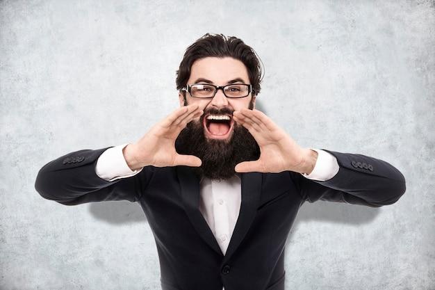 ビジネスマンが叫び、口の近くで手をつないで、背景にコンクリートの壁、行動を呼びかける概念