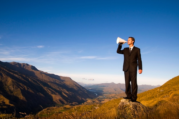 Бизнесмен кричит на вершине горы.