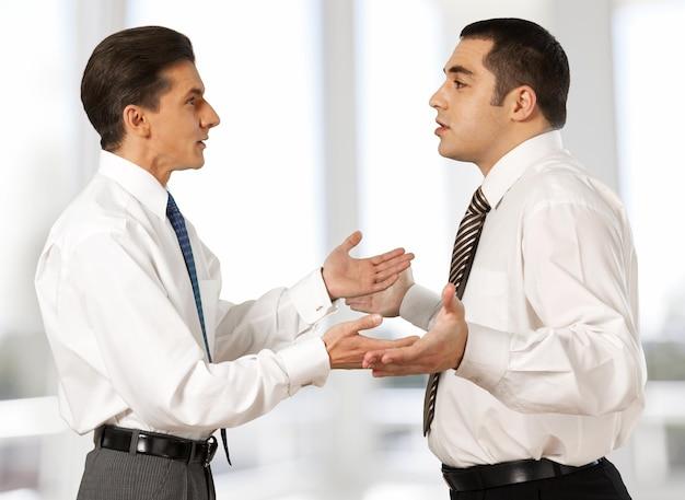 Бизнесмен выкрикивает приказы работнику на фоне