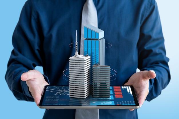 ビジネスマンは、タブレット画面に投資するための3d不動産の建物を表示します。
