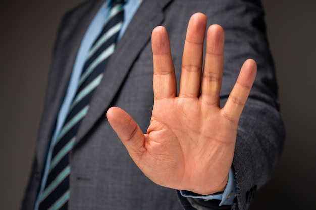 Businessman show hand sign for stop and holding, concept of professional warning for stop new investment in world crisis