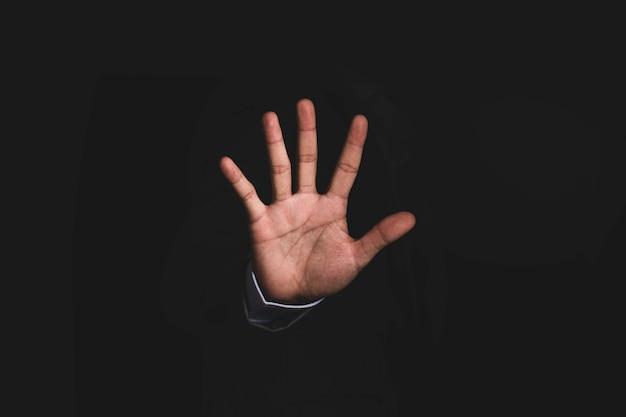 ビジネスマンは、黒い背景に「停止」、「しない」、「拒否」のジェスチャーを示します。