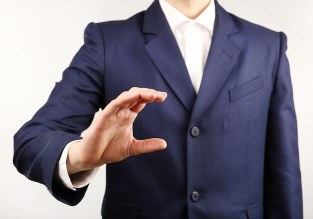 Бизнесмен показывает что-нибудь на серой стене