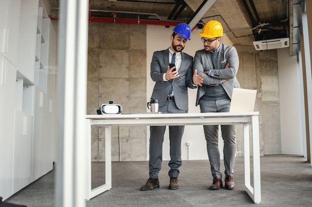 Businessman showing architect how he imagined building on the phone