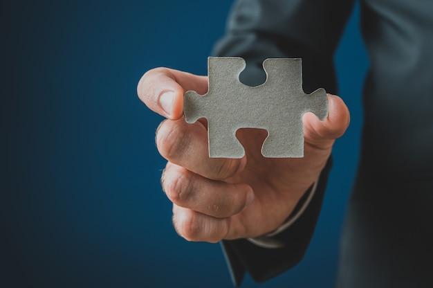Businessman showing a blank puzzle piece