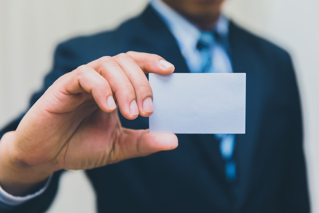 Businessman showing business card in suit