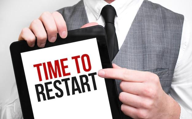 Бизнесмен, показывающий бизнес-концепцию на планшете, стоя в офисе, время для перезагрузки