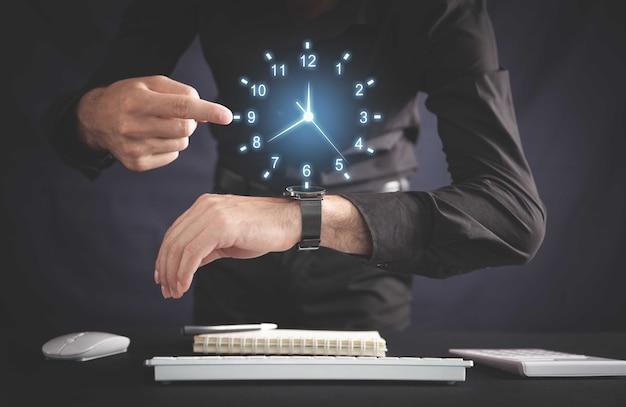 オフィスで時計を示すビジネスマン。営業時間管理